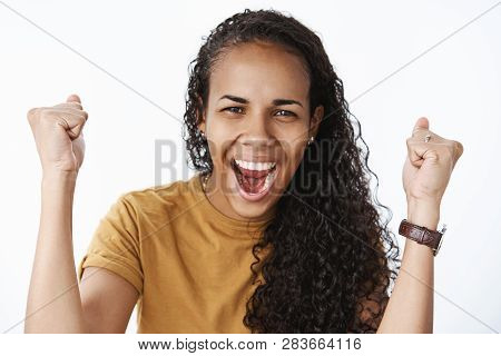 Happy and thrilled delighted african american girl with curly hair raising clenched fists in cheer and success yelling yeah and squinting joyfully receiving prize, triumphing and celebrating poster
