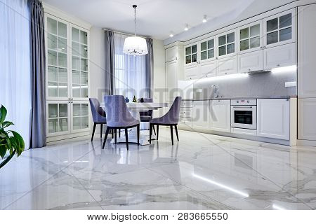 Minimalistic Interior Of Living Room In Light Tone With Marble Flooring, Large Windows And A Table F