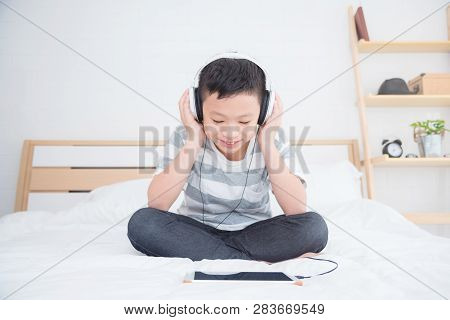 Young Asian Boy Wearing Headset Listening Music And Play Games From Tablet Computer On Bed