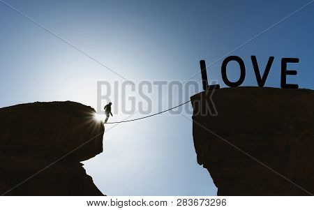 Silhouette A Man Walking On Rope Over Precipice To Love. Loves Concept