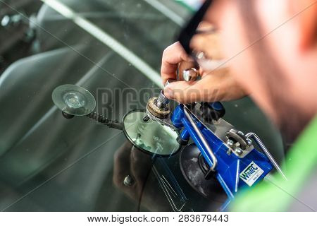 Koblenz Gerrmany 04.04.2018 Man Using Repairing Equipment To Fix Damaged Cracked Windshield At Winte