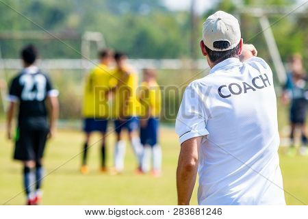 Back Of Male Football Coach Wearing White Coach Shirt At An Outdoor Sport Field Coaching His Team Du