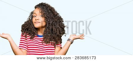 Young beautiful woman with curly hair wearing stripes t-shirt clueless and confused expression with arms and hands raised. Doubt concept.