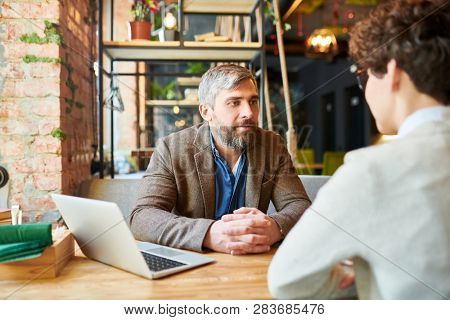 Bearded man in formalwear having talk to colleague or one of clients at meeting in cafe