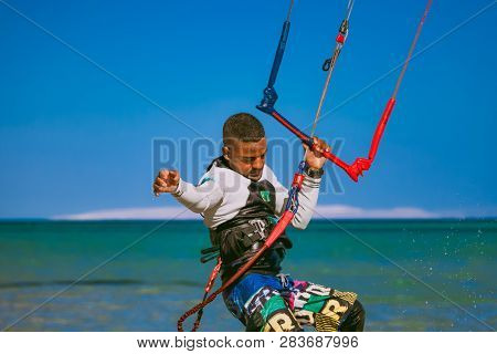 Egypt, Hurghada - 30 November, 2017: Close-up surfer holding the kite rope standing on the surfboard. Red sea background. The outdoor activity. Extreme water sport. The popular tourist attraction.