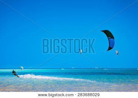 Egypt, Hurghada - 30 November, 2017: The kiter gliding over the Red sea surface. The active leisure. Picturesque marine scenery. The popular tourist water attraction. The outdoor sport activity.