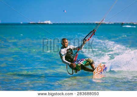 Egypt, Hurghada - 30 November, 2017: The kiter on the wakeboard holding the kite straps. The wave riding over the crystal clear Red sea surface. The professional kitesurfing. Extreme sport activity.