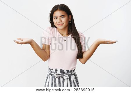 Girl Not Cares Standing Indifferent And Unbothered, Shrugging With Hands Spread Sideways Frowning An