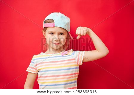 Attractive Little Girl Shows The Biceps On A Red Background. Feel So Powerful. Girls Rules Concept.
