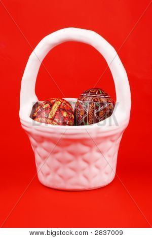 Two Easter Eggs In White Basket Over Red