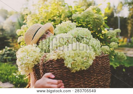 Happy Romantic Kid Girl Picking Flowers In Sunny Summer Garden