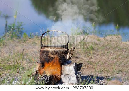 Teapot On Campfires Amongst Stone. Space For Text