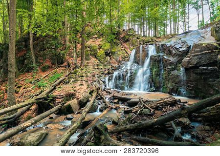 Waterfall In The Forest. Beautiful Spring Scenery. Water Comes Out Of Rocky Cliff. Fallen Trees In T