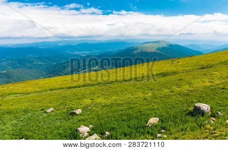 Summer Mountain Scenery. Rocks On The Grassy Meadow. Distant Ridge Beneath A Cloudy Sky. Beautiful V