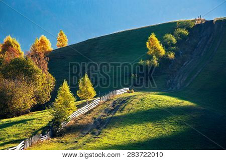 Beautiful Autumn Countryside In Mountains. Wooden Fence Along The Road Uphill. Drop Of Light On The