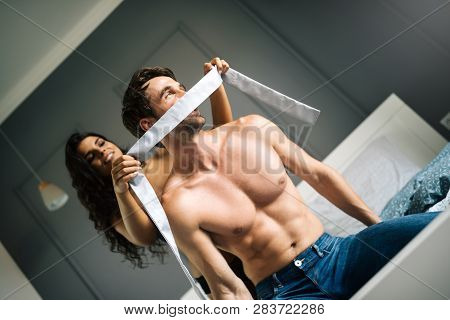 Young couple being intimate in bedroom. Sensual lovers making love in bedroom. poster