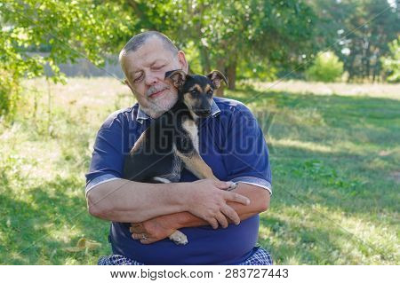 Outdoor Portrait Of Caucasian Senior Man Relaxing While Holding Black Little Puppy On The Hands