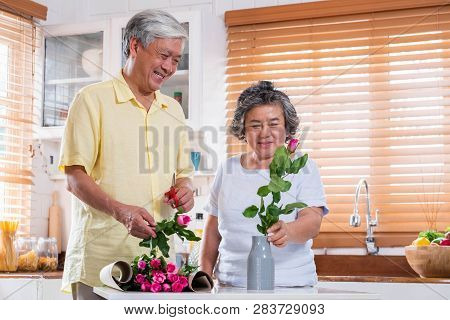 Asian Senior Couple Husband And Wife Flower Arrangement To Vase On Table In Kitchen At Home In Valen
