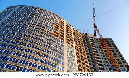 Building And Crane Under Construction. Construction Of A Modern High-rise Hotel