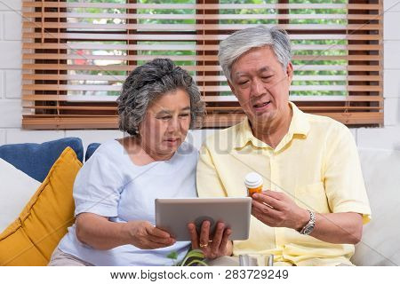 Asian Senior Couple Use Tablet Computer Searching About Doctor Pill Sitting On Sofa At Home,senior L