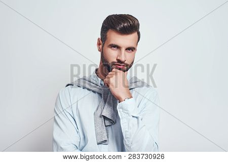 Maybe Is...close Up Portrait Of Charming Young Man With Hand On Chin Thinking About Question With Th
