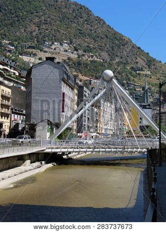 The River Valira And The Bridge La Vella  Mountains In The Background Of The Pyrenees, Andorra.