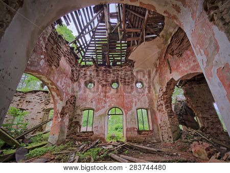 Interior View Of The Old Abandoned St. Nicholas Church Ruins In Estonia. Green Forest Covering The B