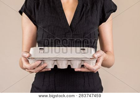 Caucasian Woman With Black Shirt Holding A Cardboard Egg Box Full Of Hen Eggs.