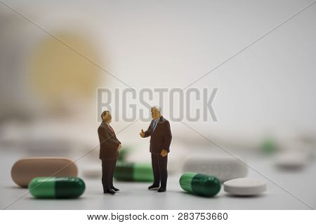 Miniature Business Men Manager Model Around With Pharmaceutical Medicines Pills And Tablets On White