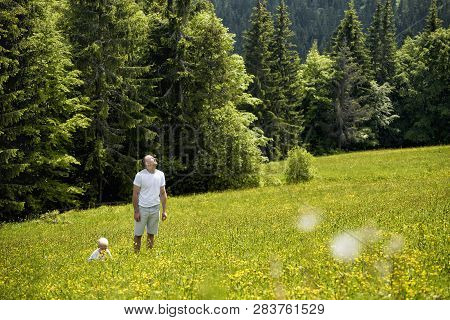 Father And Young Son Walking On A Green Meadow On A Background Of Green Pine Forests