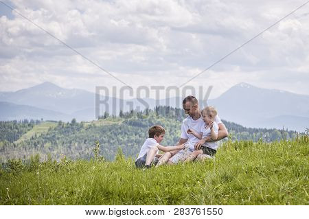 Happy Father With His Two Young Sons Sitting On The Grass On A Background Of Green Forest, Mountains