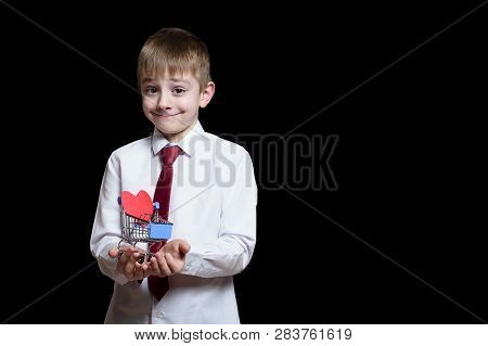 Smiling Boy In Light Shirt And Tie Holds A Metal Shopping Trolley With A Heart-shaped Postcard Insid