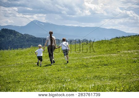 Mother And Two Young Sons Running On Green Field Holding Hands On A Background Of Green Forest, Moun