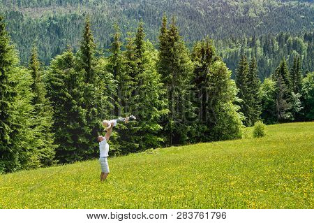 Father Throws Baby Son In The Green Meadow On A Background Of Green Pine Forests