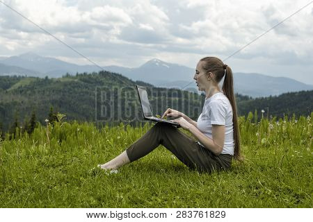 Beautiful Girl With A Laptop Sitting On Green Grass On A Background Of Mountains.