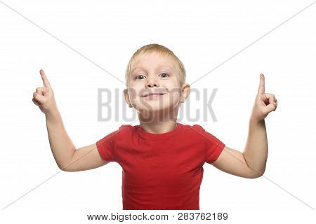 Smiling Little Blond Boy In A Red T-shirt Is Standing And Pointing With His Index Fingers Upwards. I