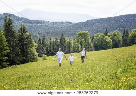 Happy Family: Father With Baby Son And Mother Walk Hand In Hand Over A Green Field Against The Backg