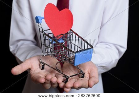 Boy Holds A Metal Shopping Trolley With A Heart Shaped Postcard Inside