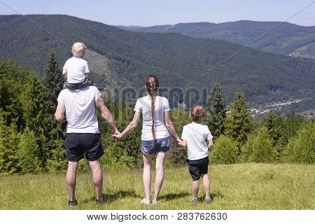 Father, Mother And Two Little Sons Are Standing On A Green Field On A Background Of Wooded Hills. Fa