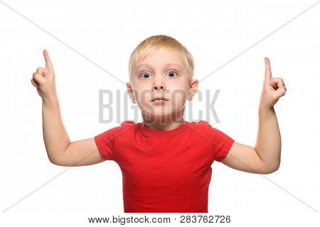 Surprised Little Blond Boy In Red T-shirt Stands And Points With Index Fingers Upwards. Isolate On W
