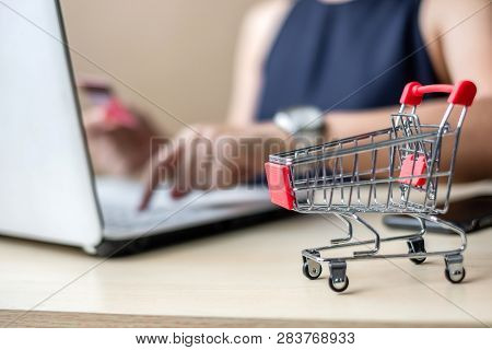 Close Up Mini Cart, Asian Businesswoman Holding Credit Card And Using Laptop For Online Shopping Whi