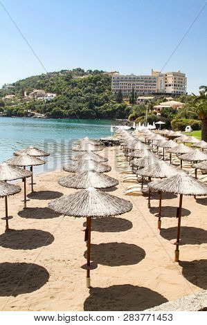 Beach With Reed Umbrellas In Corfu. Greece