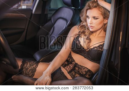 Sensual Brunette Woman Posing In Car, Looking Away.