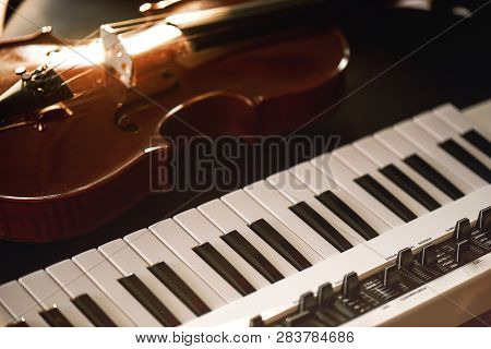 Listening Classical Music. Close-up View Of Classical Violin Instrument Lying On A Synthesizer. Musi