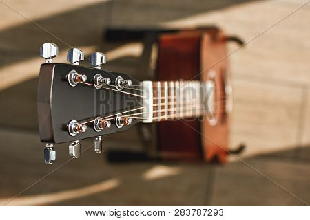Beauty Of Musical Instrument. Creative Top View Photo Of The Brown Acoustic Guitar With Focus On The
