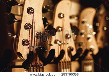 Uppermost Part Of The Guitar. Close View Of Several Acoustic Guitar Headstocks With Tuning Keys For
