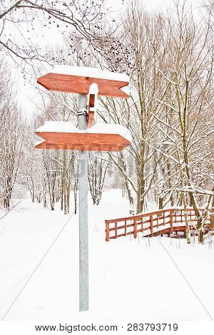 Signpost And Trees Under The Snow In A City Park
