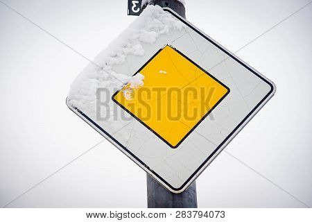 Road Sign Under The Snow Against The Sky