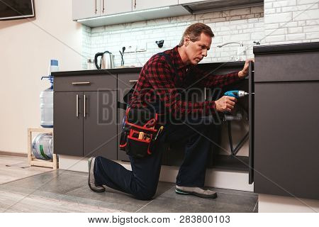 Handyman At Work. Repairing Kitchen Shelves By Perforator
