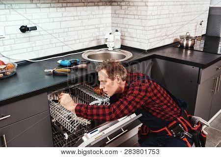 Side View Of Repairing Dishwasher. Male Technician Sitting Near Dishwasher